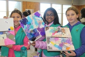 Group Girl Scouts displaying artwork created during a workshop.