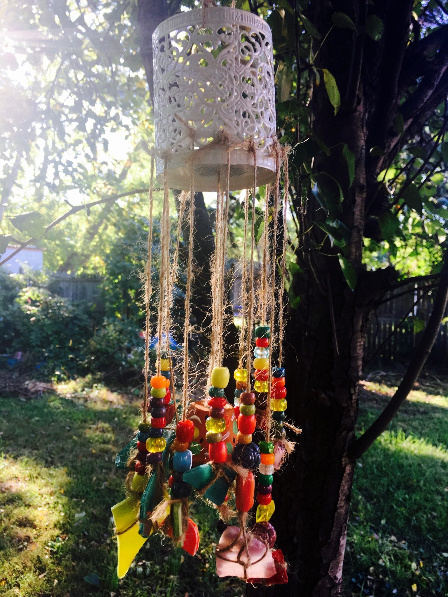 A colorful, beaded wind chime hanging from a tree created during a Girl Scout Retreat.