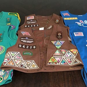 Brown vest accented with colorful patches and badges related to girl scout achievements