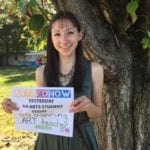 Woman smiling outdoors in front of a tree holding an Arts Ed Now campaign sign.