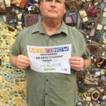 Man smiling in front of outdoor mosaic mural holding an Arts Ed Now campaign sign.