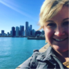 Director of Arts Education and Outreach, Kerri Sullivan, smiling with the Chicago skyline as a backdrop on a sunny day