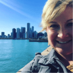 Adult woman smiling with the Chicago skyline as a backdrop on a sunny day
