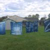 Shibori dyed fabric drying outside on clothesline at Appel Farm.