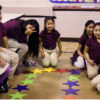 A group school children smiling and laughing while seated in a circle around colorful stars.