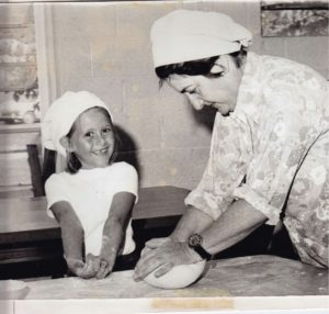 Founder Clare Appel baking in the kitchen assisted by smiling child.